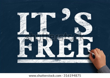 Hand with chalk is writing the text It is Free on the blue chalkboard. - stock photo
