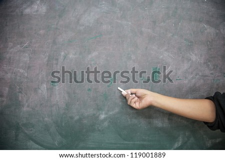 hand with chalk pointing to a blank blackboard - stock photo