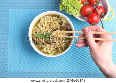 Hand with Chinese chopsticks.  Chinese noodles in soup. Soup with noodles and mushrooms. The seafood chowder. Kitchen Asia. The vegetables on the plate. Tomatoes on the branch and lettuce. - stock photo