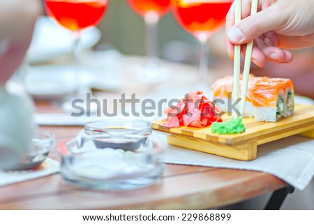 Hand with chopsticks and wasabi sushi close ginger - stock photo