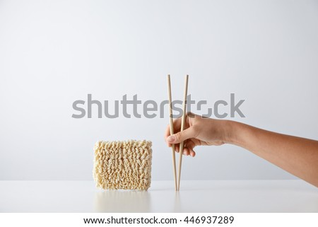 Hand with chopsticks near pack of pressed dry egg noodles isolated on white - stock photo