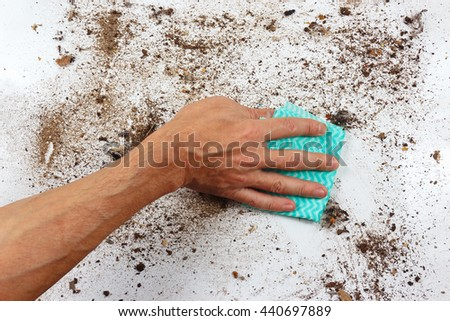 Hand with cloth cleans a very dirty surface - stock photo