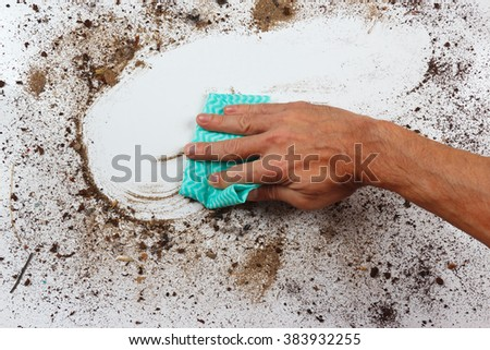 Hand with cloth wiping a very dirty surface - stock photo