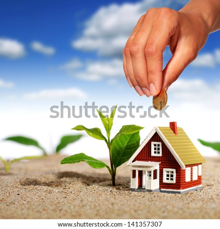 Hand with coin and house over sky background.