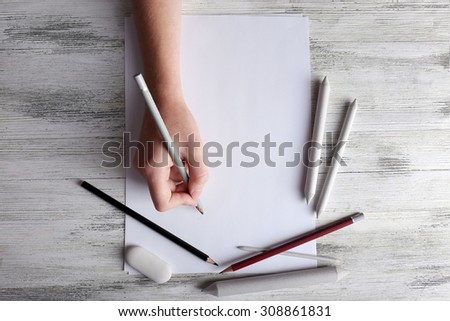 Hand with color pencils and blank sheet of paper on wooden table - stock photo
