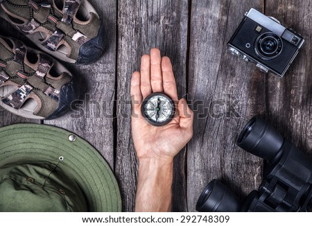 Hand with compass and traveler outfit on the wooden background - stock photo