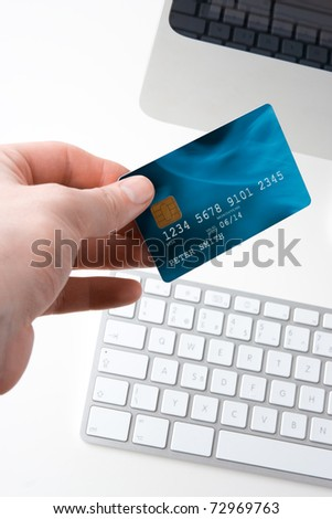 Hand with credit card and computer - electronic payment concept. Focused on credit card. I am author of image used on credit card and used data are fictitious. - stock photo