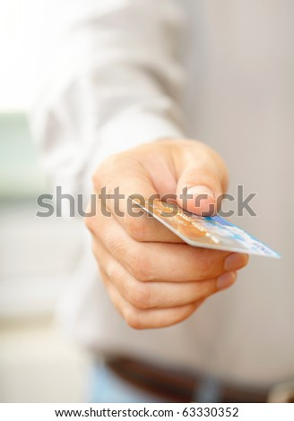 Hand with credit card. Shallow DOF - stock photo