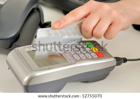 Hand with credit card swipe through terminal for sale. - stock photo
