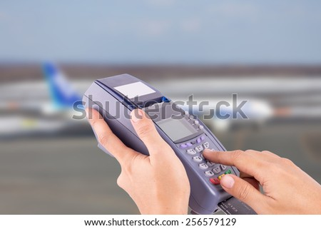 hand with credit card swipe through terminal for sale airplane ticket - stock photo