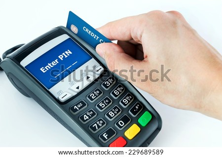 Hand with credit card swipe through terminal for sale. Enter PIN on display - stock photo