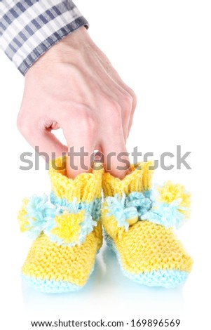 Hand with crocheted booties for baby, isolated on white - stock photo
