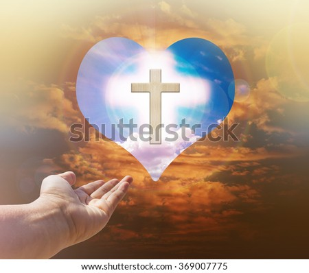Hand with crucifix or cross and god light on heart freedom sky background