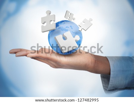 Hand with digital puzzles and a globe against a digital background - stock photo