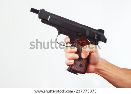 Hand with discharged gun on a white background - stock photo