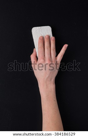Hand with dry sponge on matte gray surface - stock photo