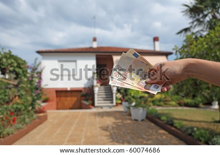 Hand with Euro notes - symbolic for rent or buy a house - stock photo