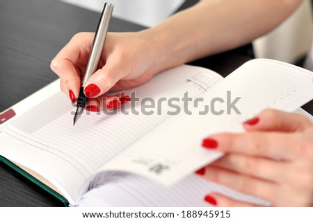 hand with fountain pen writing or signing on a blank diary - stock photo
