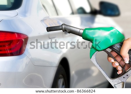 Hand with fuel pistol with new car in background - stock photo