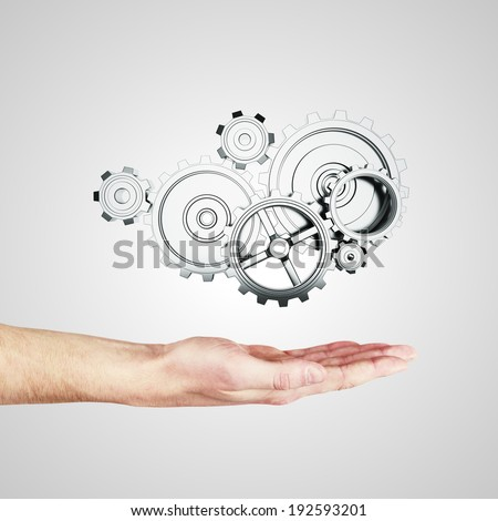 hand with  gears and cogwheels - stock photo