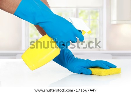 hand with glove using cleaning sponge to clean up the table - stock photo