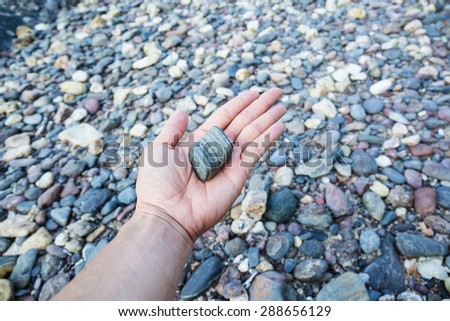 Hand with gray stone on stone background