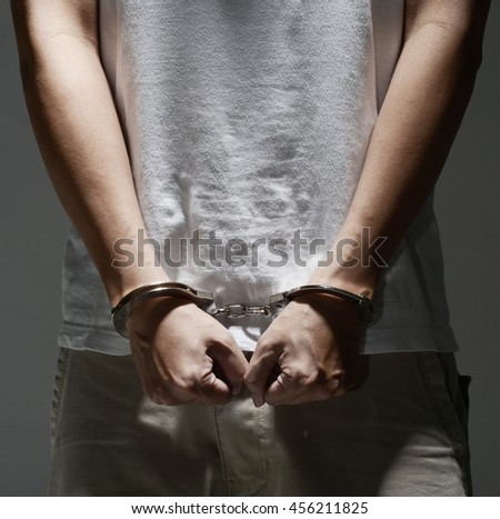 hand with handcuff, arrested criminal in low key tone
