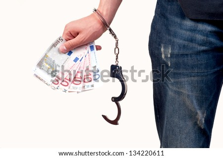 Hand with handcuffs holding money on white background - stock photo