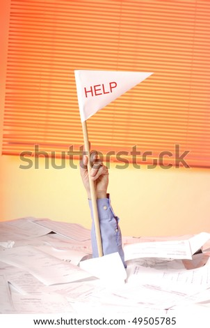 hand with help flag  sticking out of a desk full of papers - stock photo
