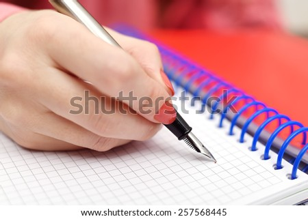 hand with ink pen writing in notebook - stock photo