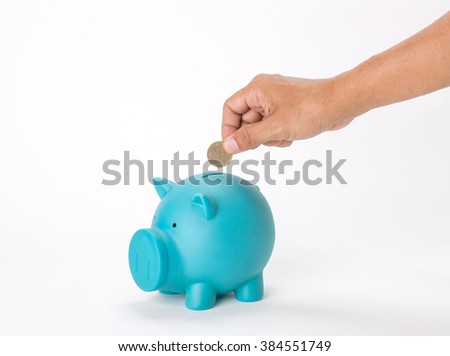 Hand with japan 500 yen coin over a blue piggy bank on white background
