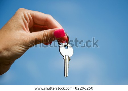 Hand with key against a blue sky - stock photo