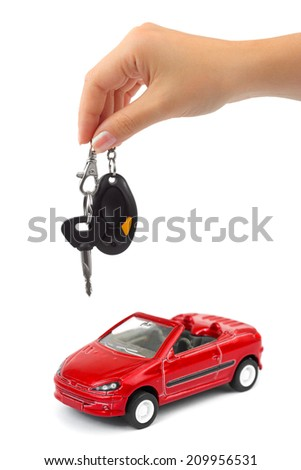 Hand with key and car isolated on white background