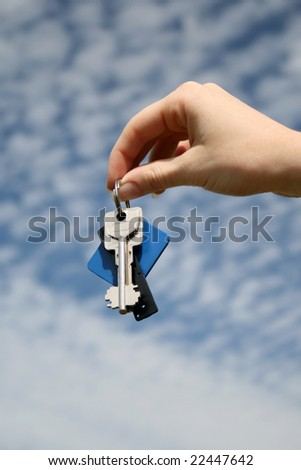 hand with key on the blue sky background - stock photo