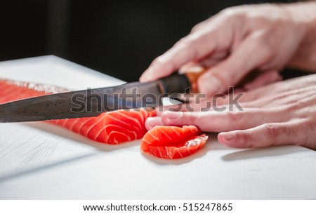 Hand with knife cuts fish. Raw fish on cooking board. Salmon meat for special dish. Chef prepares a delicacy