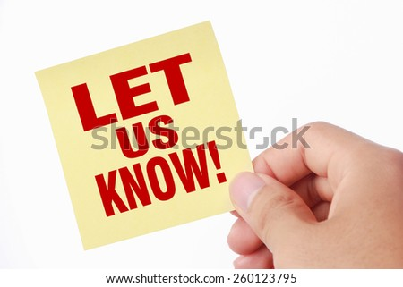 Hand with Let us know sticky note is isolated on white background.
