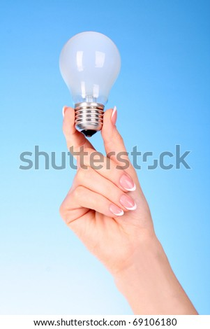 hand with lightbulb on blue background - stock photo