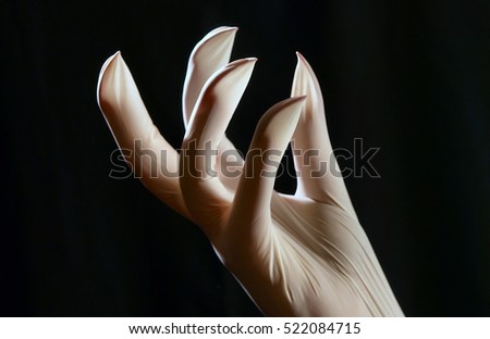 Hand with long nails wearing latex glove.