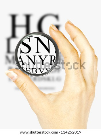 Hand with magnifier and eyesight test chart isolated on white background - stock photo