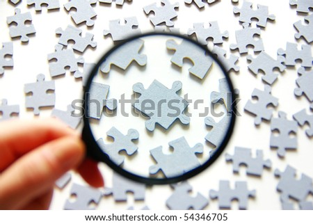 Hand with magnifying glass and puzzle - stock photo