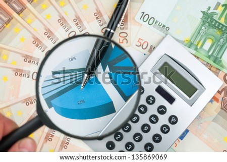 Hand with magnifying glass over a calculator, pen and money - stock photo