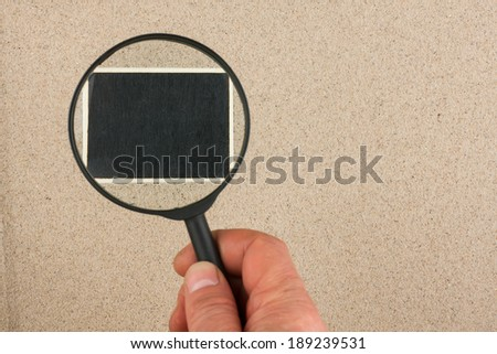 Hand with magnifying glass over the sign, in the sand, with space for your text - stock photo