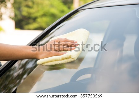 Hand with man cleaning windshield car with microfiber cloth  - stock photo