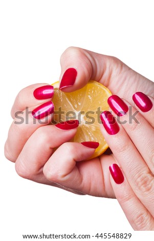 Hand with manicured nails painted deep glossy red squeeze lemon on white background