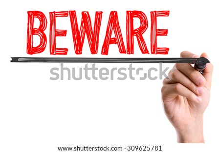 Hand with marker writing the word Beware - stock photo