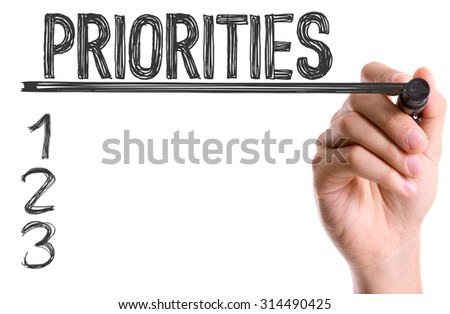 Hand with marker writing the word Priorites - stock photo