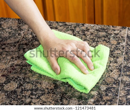 Hand with microfiber cleaning rag wiping stone counter top in kitchen - stock photo