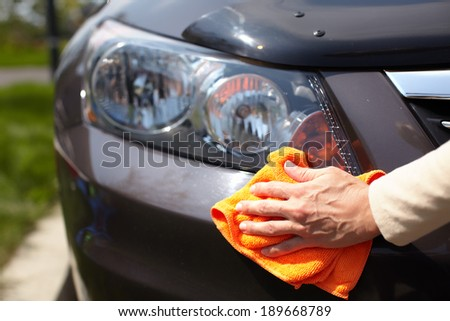 Hand with microfiber cloth cleaning car. - stock photo