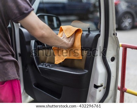Hand with  microfiber cloth cleaning the car - stock photo