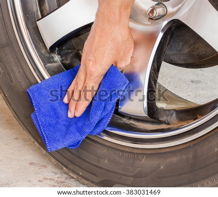 Hand with microfiber cloth cleaning wheel car. - stock photo